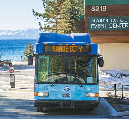 Bus in front of building in front of Lake Tahoe