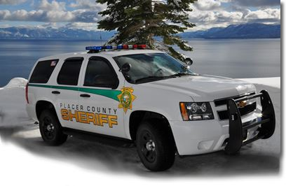 White Sheriff SUV in snow in front of lake